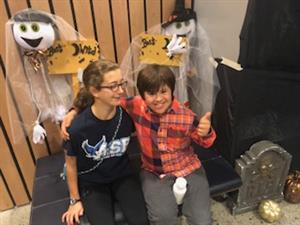 Two students sit in front of Halloween decorations