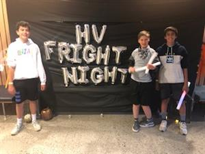 "Three students stand in front of a sign that says ""HV Fright Night"""