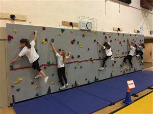 Hillview students climb the rock wall in PE.
